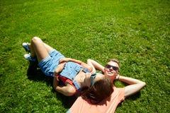 Pares adolescentes felices que mienten en hierba en el verano Foto de archivo