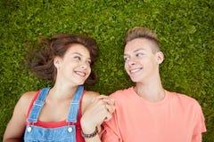 Pares adolescentes felices que mienten en hierba en el verano Fotos de archivo