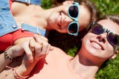 Pares adolescentes felices que mienten en hierba en el verano Fotografía de archivo