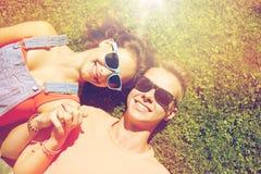 Pares adolescentes felices que mienten en hierba en el verano Imagenes de archivo