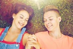 Pares adolescentes felices que mienten en hierba en el verano Fotos de archivo libres de regalías