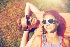 Pares adolescentes felices que mienten en hierba en el verano Fotografía de archivo libre de regalías