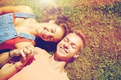 Pares adolescentes felices que mienten en hierba en el verano Foto de archivo libre de regalías