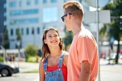 Pares adolescentes felices que miran uno a en ciudad Imagen de archivo libre de regalías