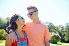 Pares adolescentes felices que miran uno a en parque Foto de archivo