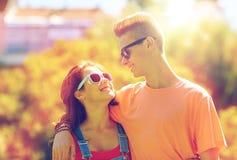 Pares adolescentes felices que miran uno a en parque Imagen de archivo