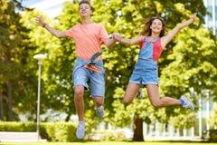 Pares adolescentes felices que saltan en el parque del verano Foto de archivo libre de regalías