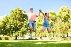 Pares adolescentes felices que saltan en el parque del verano Fotos de archivo libres de regalías
