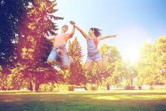 Pares adolescentes felices que saltan en el parque del verano Fotografía de archivo