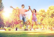 Pares adolescentes felices que saltan en el parque del verano Fotos de archivo
