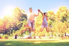 Pares adolescentes felices que saltan en el parque del verano Foto de archivo