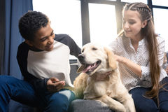 Pares adolescentes felices que se divierten con el perro del golden retriever dentro Fotografía de archivo libre de regalías