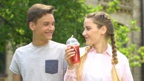 Pares adolescentes felices que se divierten junto, el chicle, soda de consumición, lento-MES almacen de metraje de vídeo
