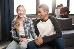 Pares adolescentes felices que se sientan en el sofá y que llevan a cabo las manos con los amigos que se colocan detrás Foto de archivo