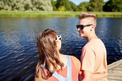 Pares adolescentes felices que se sientan en litera del río Imagenes de archivo
