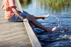 Pares adolescentes felices que se sientan en litera del río Fotos de archivo libres de regalías