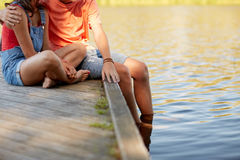 Pares adolescentes felices que se sientan en litera del río Fotografía de archivo libre de regalías