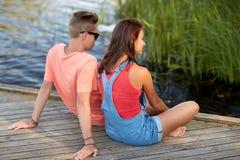 Pares adolescentes felices que se sientan en litera del río Foto de archivo