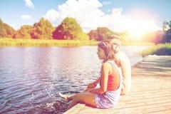 Pares adolescentes felices que se sientan en litera del río Fotografía de archivo