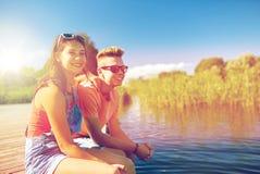 Pares adolescentes felices que se sientan en litera del río Foto de archivo libre de regalías