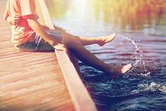 Pares adolescentes felices que se sientan en litera del río Imágenes de archivo libres de regalías