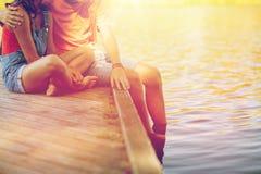 Pares adolescentes felices que se sientan en litera del río Fotos de archivo
