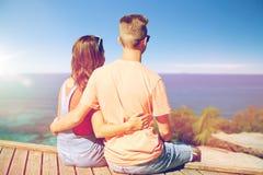 Pares adolescentes felices que se sientan en litera del río Imagen de archivo