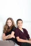Pares adolescentes felices que se sientan junto Imágenes de archivo libres de regalías