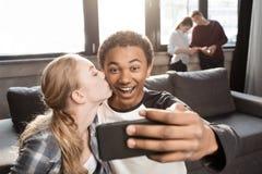 Pares adolescentes felices que toman el selfie con los amigos que se colocan detrás Imagen de archivo