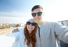 Pares adolescentes felices que toman el selfie en la calle de la ciudad Fotos de archivo libres de regalías