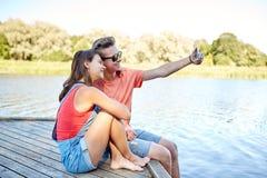 Pares adolescentes felices que toman el selfie en smartphone Imagen de archivo