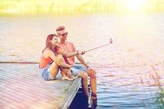 Pares adolescentes felices que toman el selfie en smartphone Imagenes de archivo