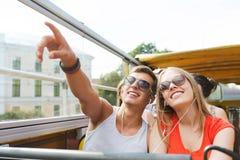 Pares adolescentes felices que viajan en bus turístico Imagen de archivo libre de regalías