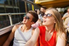 Pares adolescentes felices que viajan en bus turístico Imágenes de archivo libres de regalías