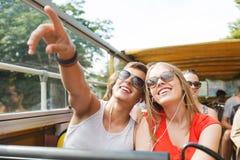 Pares adolescentes felices que viajan en bus turístico Fotografía de archivo