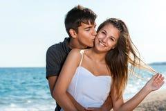 Pares adolescentes felizes que abraçam na praia. Foto de Stock