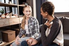 Pares adolescentes felizes que sentam-se junto e que guardam as mãos dentro Imagem de Stock Royalty Free