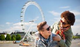 Pares adolescentes felizes que têm o divertimento sobre Londres Fotografia de Stock