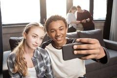 Pares adolescentes felizes que tomam o selfie com os amigos que estão atrás Fotografia de Stock