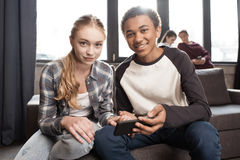 Pares adolescentes felizes usando o smartphone no sofá quando amigos que estão atrás Fotos de Stock