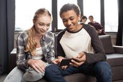 Pares adolescentes felizes usando o smartphone no sofá quando amigos que estão atrás Imagens de Stock Royalty Free