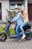 Pares adolescentes jovenes atractivos en una motocicleta Imágenes de archivo libres de regalías