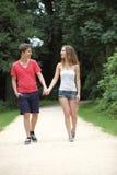 Pares adolescentes jovenes atractivos que caminan una fecha Imágenes de archivo libres de regalías