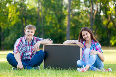 Pares adolescentes jovenes con la pizarra Foto de archivo
