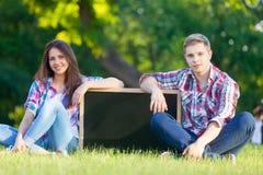 Pares adolescentes jovenes con la pizarra Imagen de archivo libre de regalías