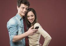 Pares adolescentes jovenes con smartphone Imágenes de archivo libres de regalías
