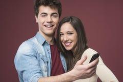 Pares adolescentes jovenes con smartphone Fotos de archivo libres de regalías