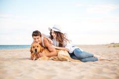 Pares adolescentes jovenes con un perro que se sienta en la playa Imágenes de archivo libres de regalías