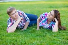 Pares adolescentes jovenes en el verde Fotos de archivo libres de regalías