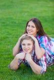 Pares adolescentes jovenes en el verde Imágenes de archivo libres de regalías